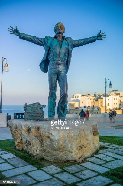 The statue of Domenico Modugno born in Polignano a Mare in a village square in Puglia southern Italy