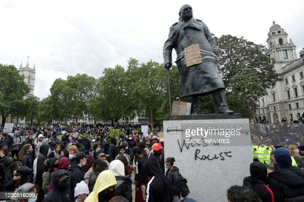 """The statue of former British prime minister Winston Churchill is seen defaced, with the words """"was a racist"""" written on it's base in Parliament..."""