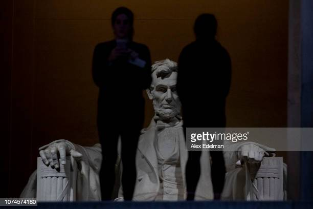 The statue of former President Lincoln looms in the distance as tourists visit the Lincoln Memorial on December 22 2018 in Washington DC A partial...