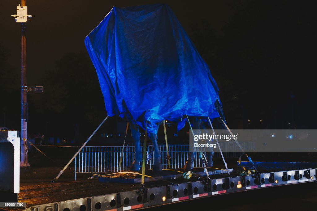 The statue of General Nathan Bedford Forrest sits under a tarp on a truck after being removed from a park at night in Memphis, Tennessee, U.S., on Wednesday, Dec. 20, 2017. The City Council voted unanimously on Wednesday to sell two Memphis parks where Confederate statues were located. The parks were sold to Greenspace Inc. for $1,000 each, according to The Commercial Appeal. Photographer: Houston Cofield/Bloomberg via Getty Images
