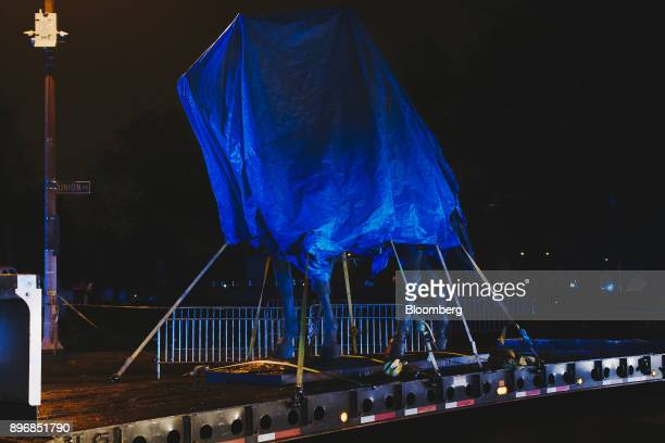 The statue of General Nathan Bedford Forrest sits under a tarp on a truck after being removed from a park at night in Memphis Tennessee US on...