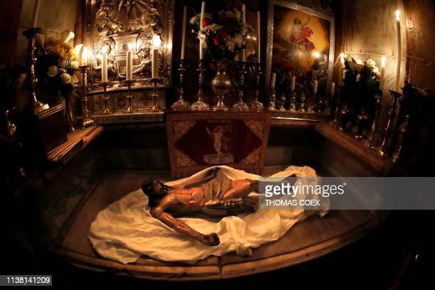 The statue of Jesus rests on the marble inside the Tomb of Christ after a reenactment of the Funeral of Jesus in the Church of the Holy Sepulchre...