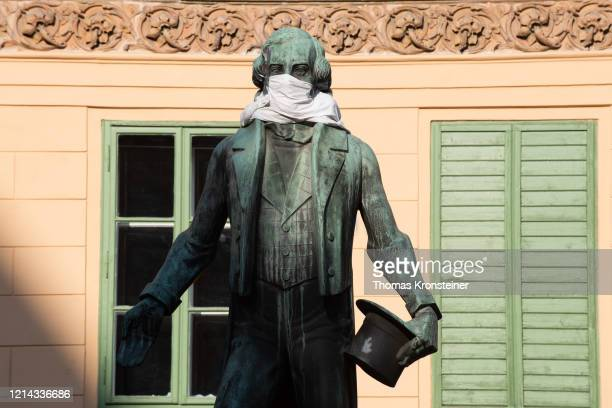 The statue of Johann Nestroy adorned with a protective mask on March 23 in Vienna, Austria. The coronavirus and the disease it causes, covid-19, are...