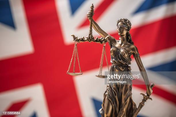 the statue of justice, goddess of justice in front of uk flag. - law stock pictures, royalty-free photos & images