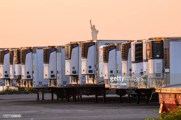 The Statue of Liberty is seen behind refrigeration trucks that function as temporary morgues at the South Brooklyn Marine Terminal during the...