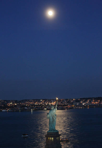 The Statue of Liberty is seen beneath the rising moon on August 12, 2011...