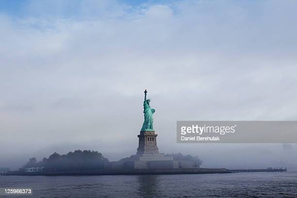 The Statue of Liberty is seen through fog prior to the start of the 125th Anniversary of the Statue of Liberty ceremony on Liberty Island on...