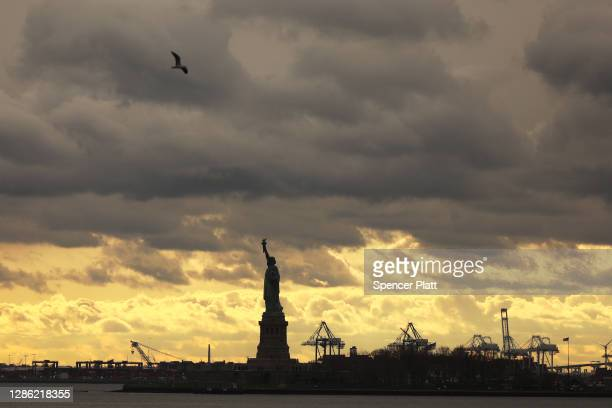 The Statue of Liberty, one of New York City's top tourist attractions, stands in New York Harbor as visits to the landmark have been restricted on...