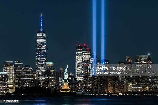 The Statue of Liberty shines on September 11, 2021 near the Tribute in Light as part of the commemoration for 20th anniversary of the terrorist...
