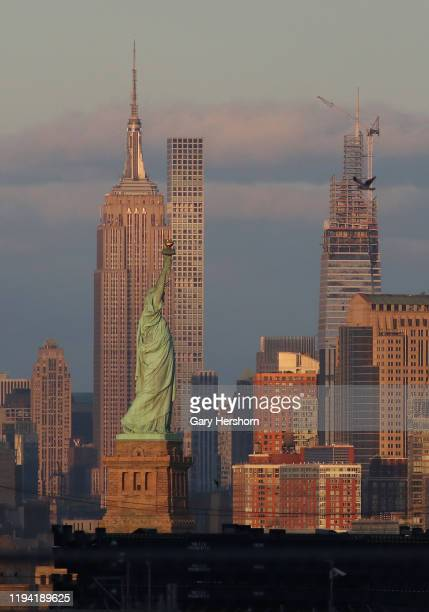 The Statue of Liberty stands in front of the Empire State Building 432 Park Avenue and One Vanderbilt as the sun sets in New York City on December 15...