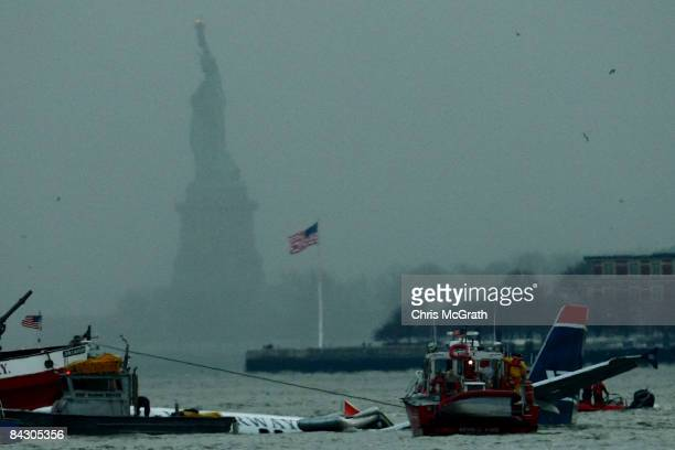 The statue of liberty stands in the background as rescue boats float next to a US Airways plane floating in the water after crashing into the Hudson...