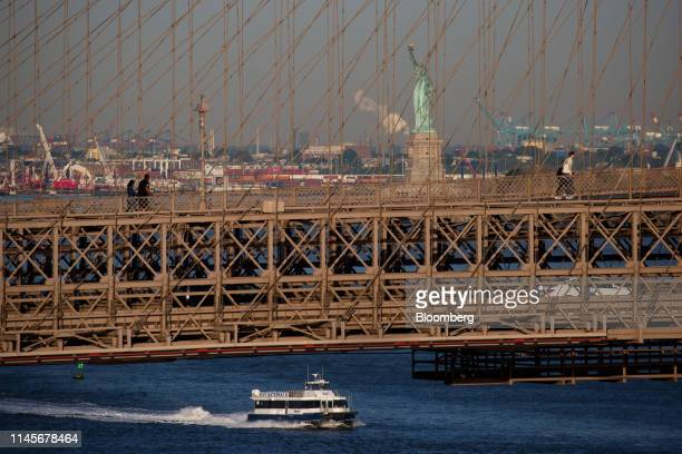 The Statue of Liberty stands past the Brooklyn Bridge in New York US on Wednesday May 22 2019 Stocks slumped globally on Thursday and traders took...