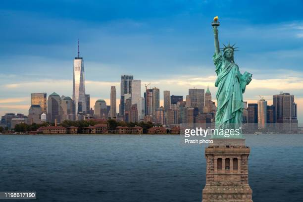 the statue of liberty with downtown new york skyline panorama with ellis island in the foreground at night in new york city, usa. - 自由の女神 ストックフォトと画像