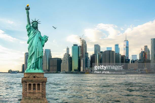 the statue of liberty with manhattan in new york city, usa - statue of liberty stock pictures, royalty-free photos & images