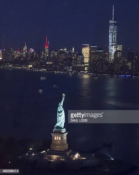 The Statue of Liberty with the Manhattan skyline in the background including One World Trade Center and the Empire State Building is seen at night...