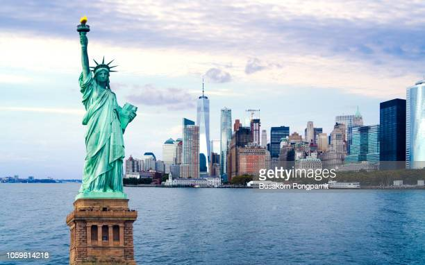 the statue of liberty with world trade center background, landmarks of new york city - stad new york stockfoto's en -beelden