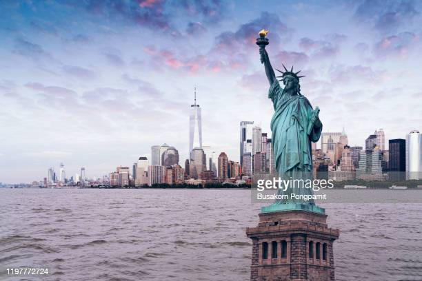 the statue of liberty with world trade center background, landmarks of new york city - monument stock pictures, royalty-free photos & images
