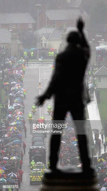 The statue of Lord Carson is pictured as the funeral cortege for footballer George Best makes its way from the service at Stormont Parliament...