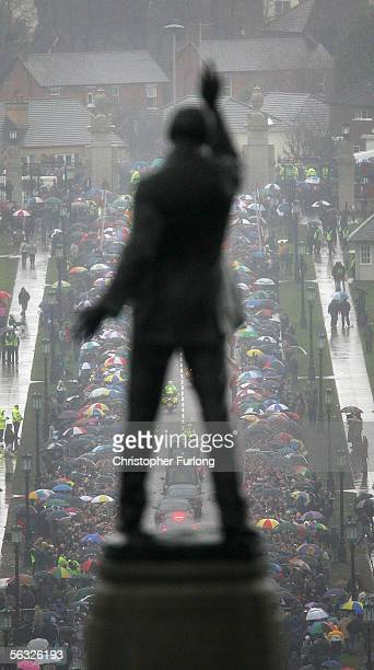 The statue of Lord Carson is seen in the foreground as the funeral cortege for footballer George Best makes its way from the service at Stormont...