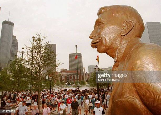 The statue of Olympics founder French Baron Pierre de Coubertin stands over crowd at the Opening ceremony of the Olympic Centennial Park 13 July in...