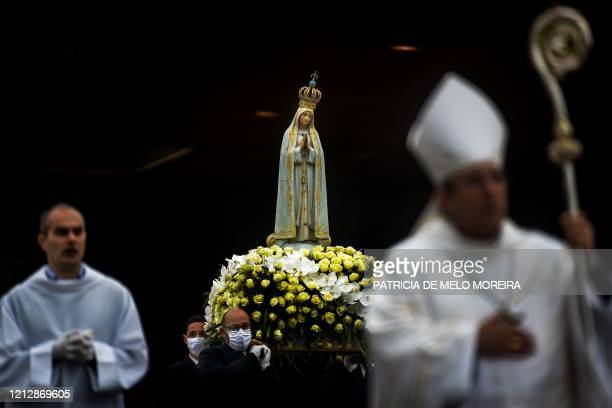 The statue of Our Lady Fatima is carried by people wearing face masks during the 103rd anniversary of the apparitions of Our Lady Fatima at the...