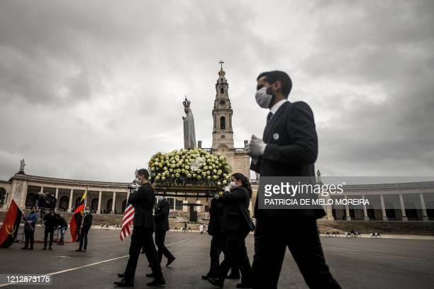 The statue of Our Lady of Fatima is carried by people wearing face masks during the 103rd anniversary of the apparitions of Our Lady Fatima at the...