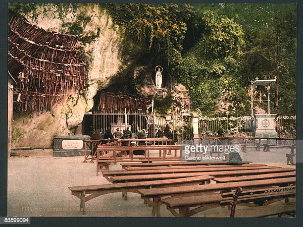 The statue of Our Lady of Lourdes in the grotto of Notre Dame in Lourdes in the French Pyrenees circa 1900 Hanging near the grotto are the crutches...