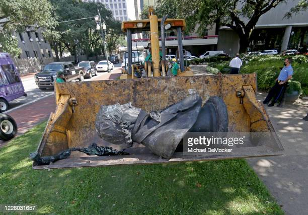 The statue of slaveholder John McDonough is removed by city workers after it was pulled from its pedestal in Lafayette Park downtown on JULY 10, 2020...