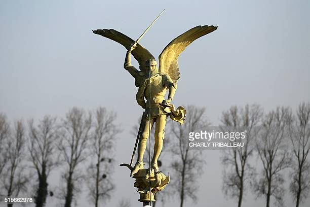 The statue of the Archangel Michael airlifted by a helicopter from the top of Mont SaintMichel Abbey is place on the ground on March 15 2016 The...