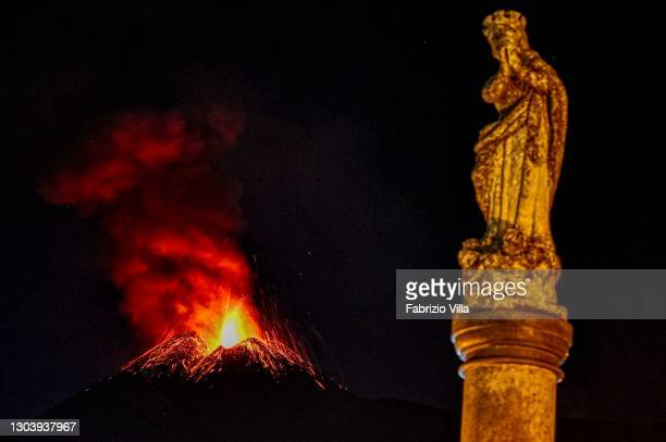The statue of the Immaculate Madonna in Milo is shown lit in the shadow of Mount Etna, which has been spewing lava, ash and volcanic rock on a...