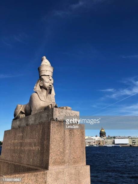 the statue of the sphinx on the background of the neva and st. isaac's cathedral - monumento fotografías e imágenes de stock