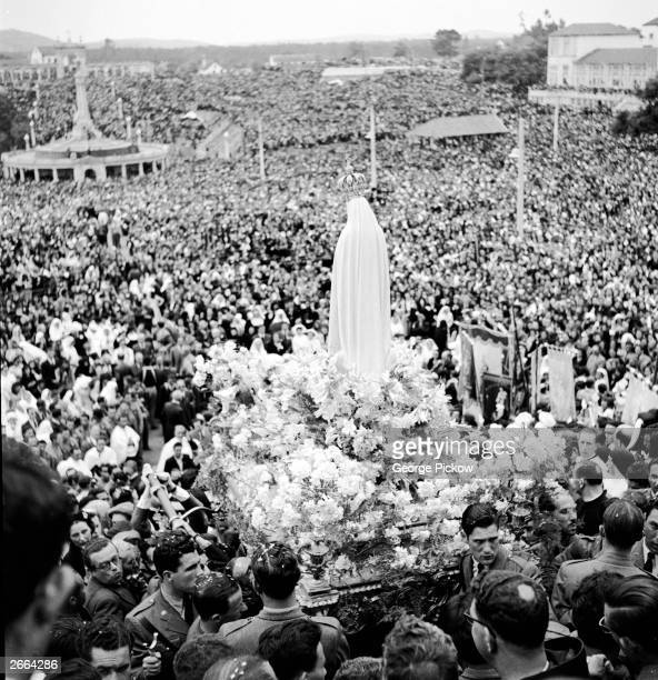 The statue of the Virgin of Fatima is bedecked with flowers and carried in procession through the crowd at Fatima Portugal