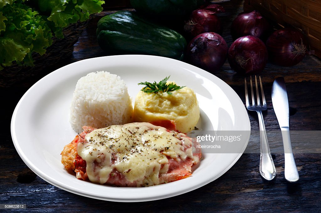 The steak parmigiana with potato and rice : Stock Photo