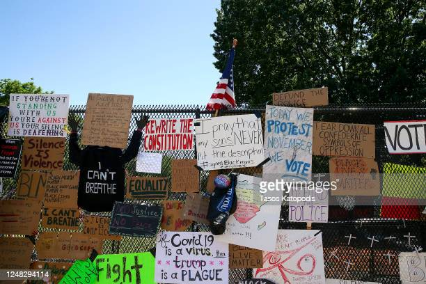 """The steel fence at Lafayette Park has become a makeshift memorial at 16th street after """"Defund The Police"""" was painted on the street near the White..."""
