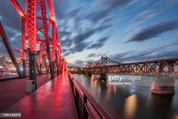 the steel railway bridge across the yalu river in the sunset. - yalu river stock pictures, royalty-free photos & images