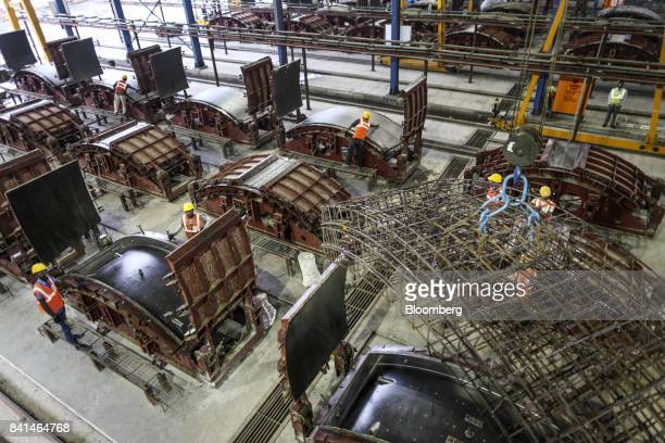 The steel reinforcing frame of a precast concrete tunnel segment is maneuvered by crane to a mold at the Mumbai Metro Rail Corp casting yard in...