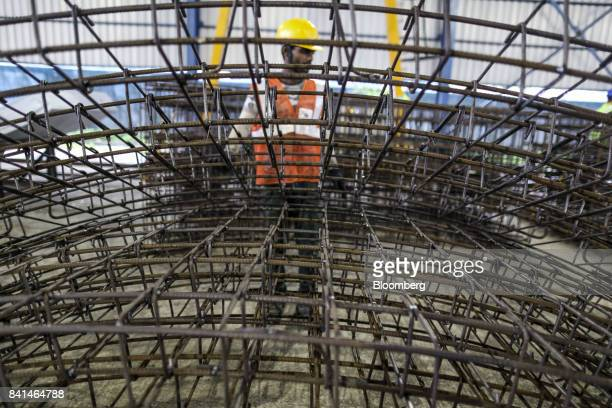 The steel reinforcing frames of precast concrete tunnel segments sit stacked at the Mumbai Metro Rail Corp casting yard in Mumbai India on Monday Aug...