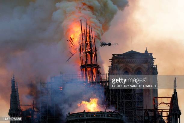 The steeple and spire collapses as smoke and flames engulf the Notre-Dame Cathedral in Paris on April 15, 2019. - A huge fire swept through the roof...