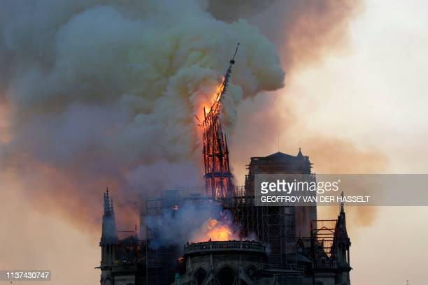 The steeple and spire engulfed in flames collapses as the roof of the Notre-Dame de Paris Cathedral burns on April 15, 2019 in Paris. - A colossal...