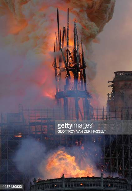 The steeple and spire engulfed in flames collapses as the roof of the NotreDame de Paris Cathedral burns on April 15 2019 in Paris A colossal fire...