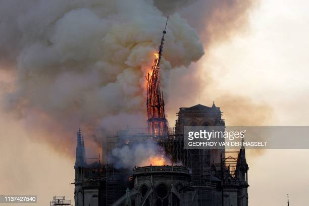 TOPSHOT The steeple and spire of the landmark NotreDame Cathedral collapses as the cathedral is engulfed in flames in central Paris on April 15 2019...