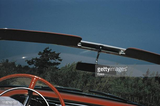 The steering wheel windscreen and rear view mirror are seen as the view from the drivers seat in a sports car parked somewhere in rural America 1957