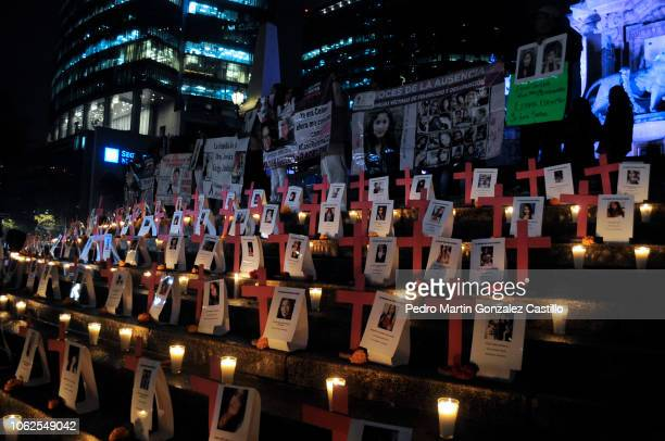 The steps of the Monument to Independence are lit with candles next to pictures of the victims during a protest of the 'Los Machos Nos Matan En...