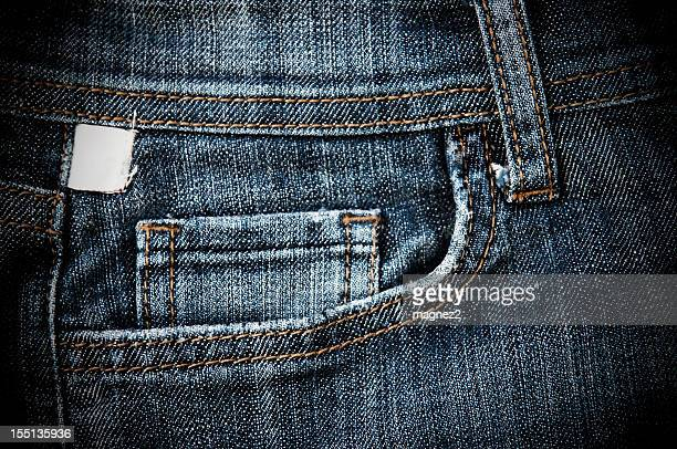 The stitched front pocket of a pair of denim jeans