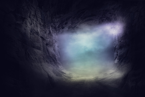 the stone cave inside. out way with spooky mist and fog 1077224936