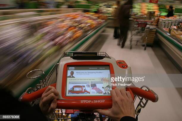 A shopper starts by scanning a loyalty card over a barcode reader on the grocery cart's computer which Stop Shop calls 'the shopping buddy' The...
