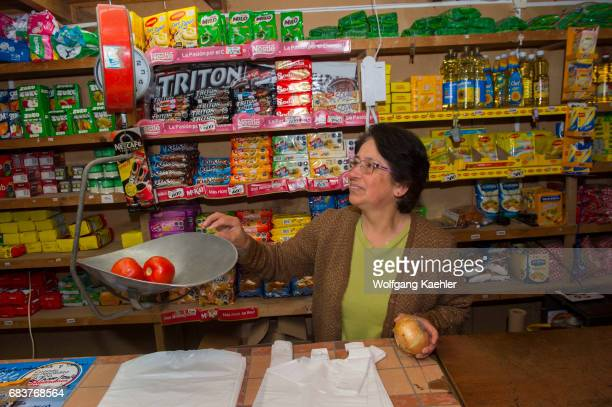 The store owner is weighing tomatoes in a small convenient store in the small village of Pargua in the Lake District of Chile