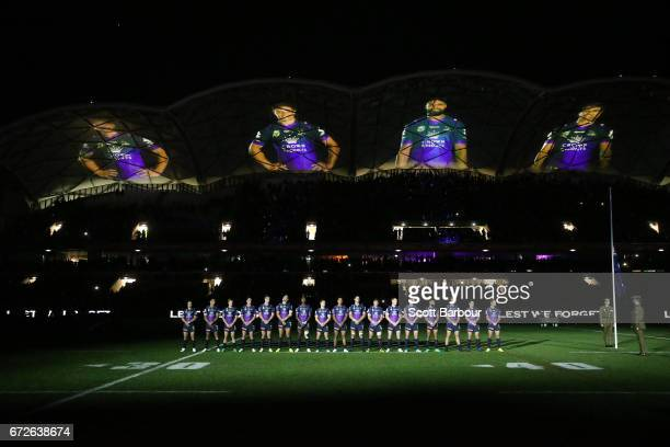 The Storm stand for a minutes silence in front of a light show by Stav Hatzipantelis during the round eight NRL Anzac Day match between the Melbourne...