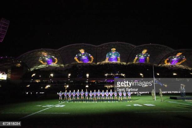 The Storm stand for the playing of The Last Post during the round eight NRL Anzac Day match between the Melbourne Storm and the New Zealand Warriors...
