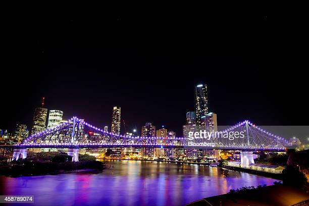 The Story Bridge stands illuminated at night over the Brisbane River in front of buildings in the central business district of Brisbane Australia on...